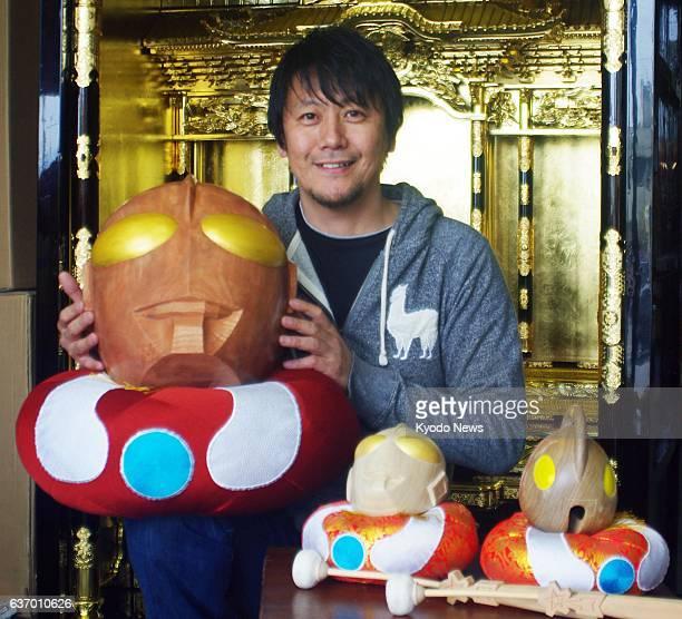 Kota, Japan - Kazuaki Tsuzuki, owner of a Buddhist altar fittings store, holds a wooden drum shaped as Ultraman, the Japanese sci-fi superhero, in...