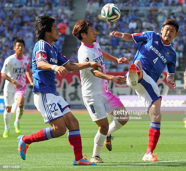 Kota Mizunuma of Sagan Tosu competes for the ball against Yuzo Kurihara and Yuji Nakazawa of Yokohama FMarinos during the JLeague match between...