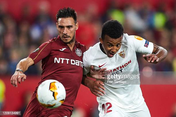 Kounde of Sevilla FC competes for the ball with Cristian Manea of CFR Cluj during the UEFA Europa League round of 32 second leg match between Sevilla...