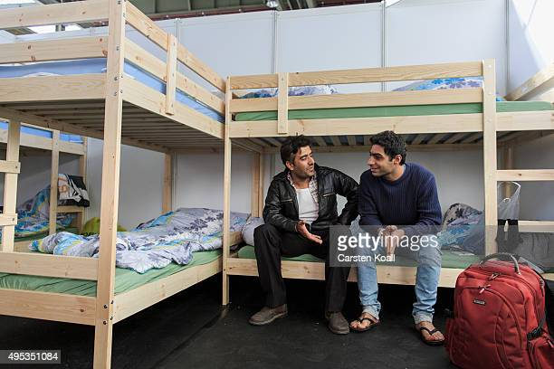 Kourosh and Babak migrants from Iran seeking asylum in Germany sitting on a bed inside a sleeping box during a press tour inside Hangar 3 at former...