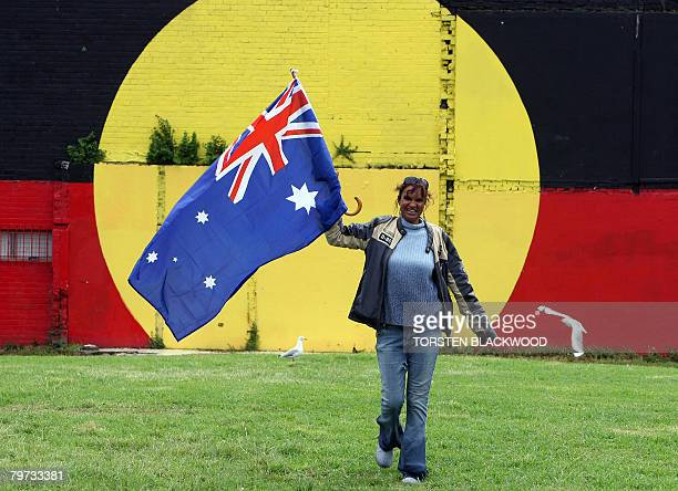 Kowanyama Aborigine MaryJane Holness proudly displays the national flag after hearing Australian Prime Minister Kevin Rudd deliver an historic...