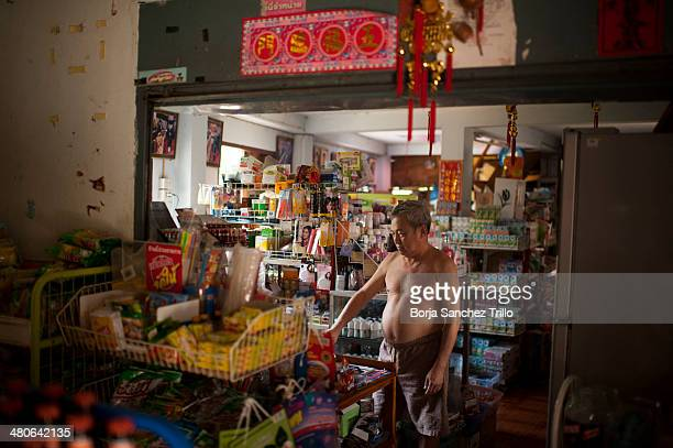 Kowit Ew a gold buyer weighs gold in his food store in Wang Kaeo on March 25 2014 in Lampang Thailand Thai villagers from Wang Nuea North of Thailand...