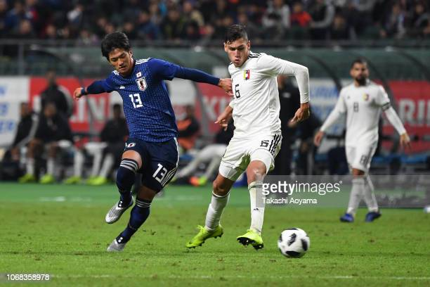 Koya Kitagawa of Japan and Nahuel Ferraresi of Venezuela compete for the ball during the international friendly match between Japan and Venezuela at...