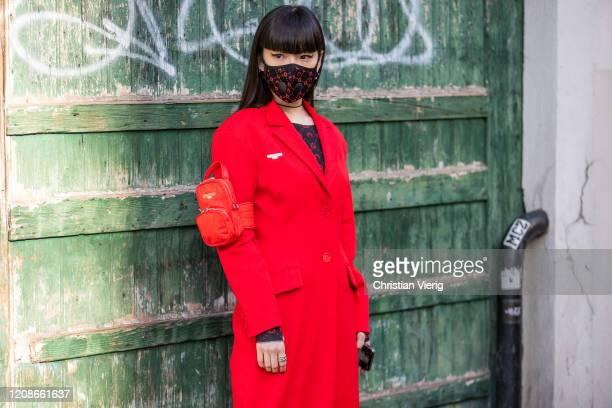 Kozue Akimoto is seen wearing face mask, red coat outside Marine Serre during Paris Fashion Week - Womenswear Fall/Winter 2020/2021 : Day Two on...