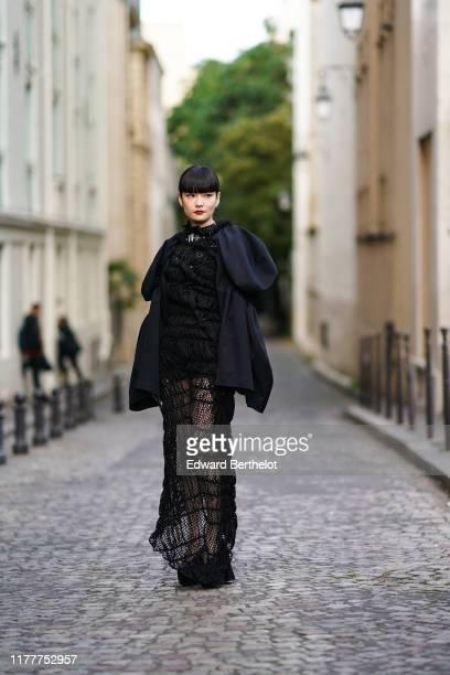 Kozue Akimoto wears a black lace mesh dress with ruffles and puff sleeves, outside CDG Comme des Garçons, during Paris Fashion Week - Womenswear...