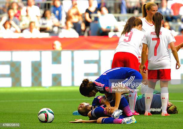Kozue Ando of Japan lies injured while Yuki Ogimi speaks to her after colliding with Gaelle Thalmann of Switzerland during the FIFA Women's World Cup...