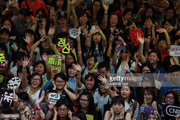 KPop fans holding signs with the names of their favourite KPop groups cheer and shout outside the venue of the KPop Festival Music Bank concert which...