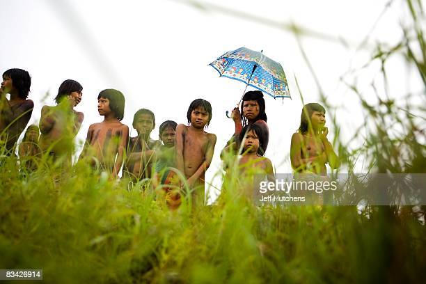 Kraho tribal men women and children huddle together under umbrellas in the rain to watch helicopters landing in their remote Kraho tribal village...