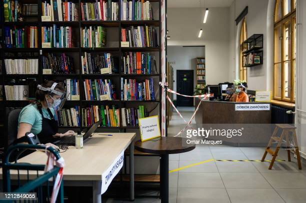 Krakow Library staff wears a protective mask face shield and gloves as she checks online orders for books at the recently renewed Krakow library...