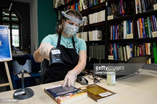 Krakow Library staff wears a protective mask face shield and gloves as she checks in a delivered book at the recently renewed Krakow library number 3...