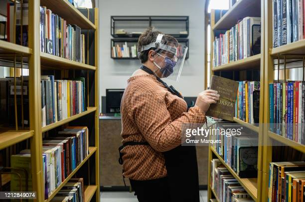 Krakow Library staff wears a protective mask face shield and gloves as she picks a reserved book at the recently renewed Krakow library number 3...