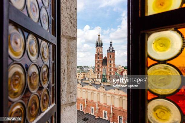 krakow skyline with st mary's church seen through an open window, poland - poland stock pictures, royalty-free photos & images