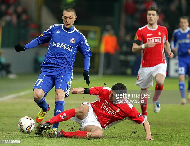 Krakow's Ivica Iliev is tackled by Liege's Karim Belhocine during an UEFA Europa League round of 32 football match between Standard de Liege and...