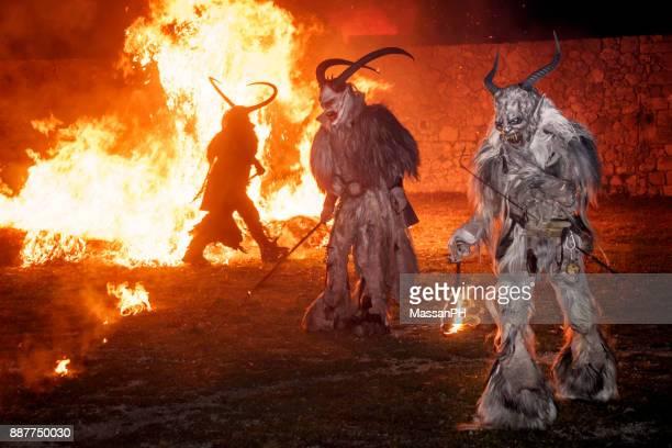 krampus band raid around the flames in the fortress of osoppo - krampus stock-fotos und bilder