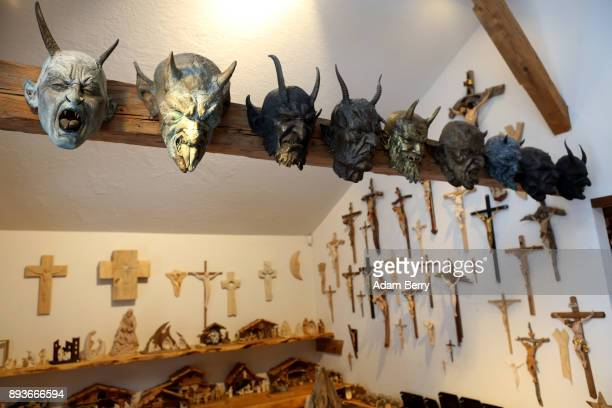 Krampus masks hang in front of crucifixes for sale in a shop belonging to sculptor and woodworker Rupert Kreuzer on December 15 2017 in Grossarl near...