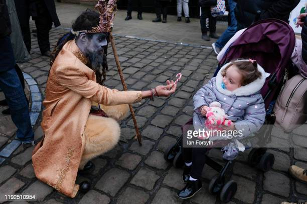 Krampus participant offers a candy cane to a young child as they walk through the streets during the annual Whitby Krampus parade on December 07 2019...