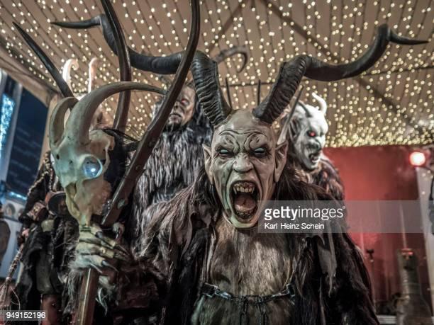 krampus with mask, horns and fur clothing at the christmas market, leoben, styria, austria - krampus stock-fotos und bilder