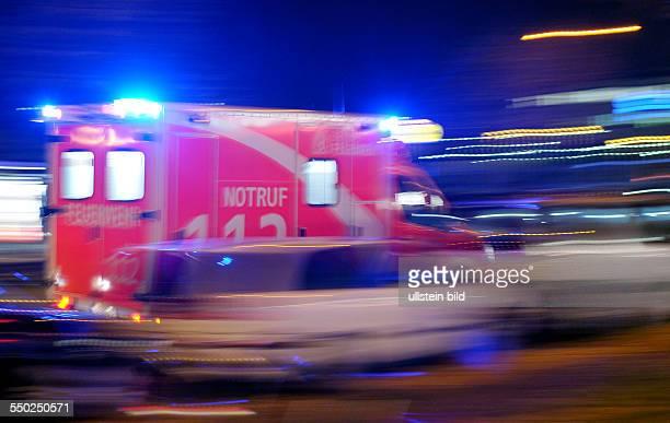 Krankenwagen rast mit Blaunicht durch das nächtliche Berlin