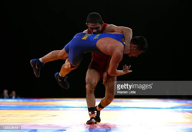 Krasimir Krastanov of Great Britain lifts Qi Mude of China during the Men's Freestyle 55kg bout during the Wrestling LOCOG Test Event for London 2012...