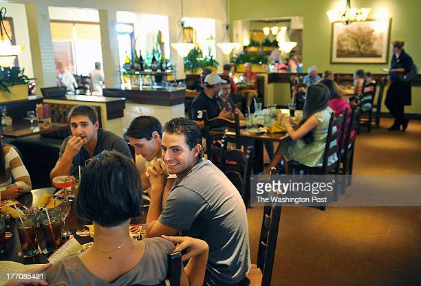 Krasimir Pehlivanov left to center Dobrina Lyanguzova back to camera Hunter Sperling and Chris Hoffman dine at Olive Garden Italian Restaurant on...