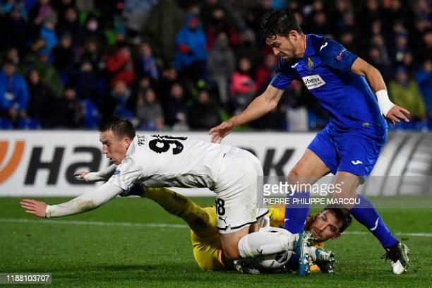 FK Krasnodar's Russian goalkeeper Stanislav Kritsyuk saves the ball as FK Krasnodar's Russian defender Sergei Petrov vies with Getafe's Spanish...