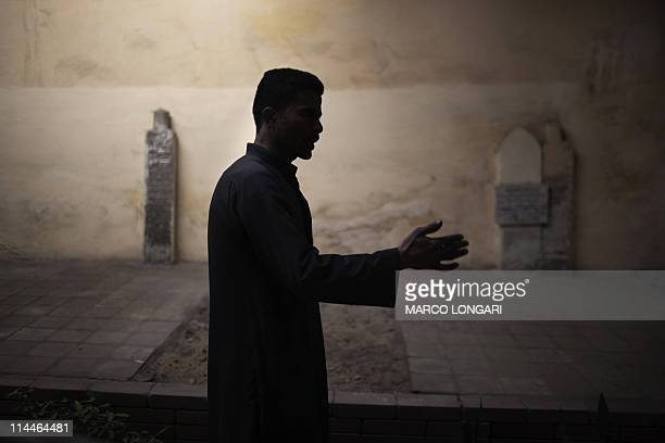 KRAUSSEgyptian grave digger Tareq Salah stands at the compound he squats at the City of the Dead in Cairo on February 15 2011 In a sprawling cemetery...