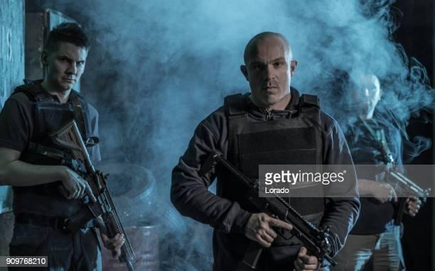 Krav Maga fighting group posing for team picture during training in dark indoor urban setting