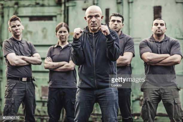 Krav Maga fighting group posing in grimy outdoor urban setting