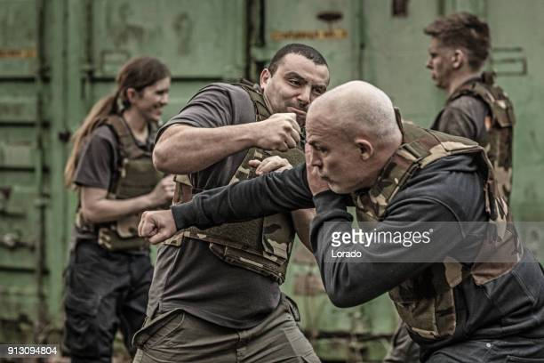 Krav Maga fighting group sparring during training session in grimy outdoor setting