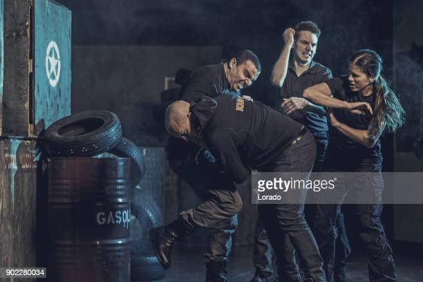 krav maga fighting group training in dark indoor urban setting - punching stock pictures, royalty-free photos & images