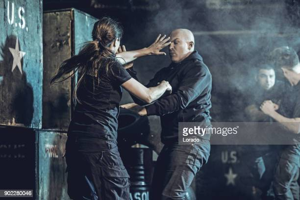Krav Maga fighting group training in dark indoor urban setting