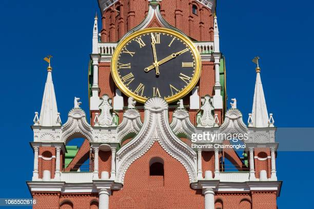 kremlin clock on the spasskaya tower of kremlin palace against blue sky in moscow,russia - モスクワ ストックフォトと画像