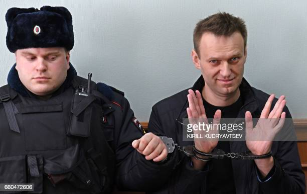 Kremlin critic Alexei Navalny, who was arrested during March 26 anti-corruption rally, gestures during an appeal hearing at a court in Moscow on...