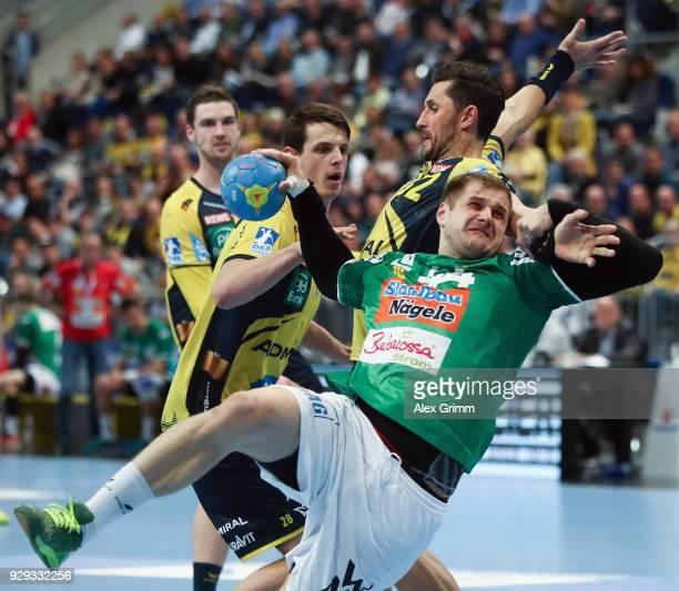 Kresimir Kozina of Goeppingen is challenged by Alexander Petersson and Hendrik Pekeler of RheinNeckar Loewen during the DHL HBL match between...
