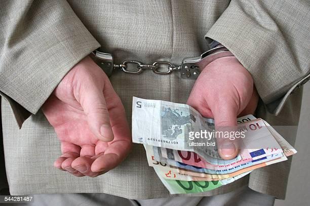 Kriminalität Wirtschaftskriminalität Festnahme Geschäftsmann in Handschellen und Euro Geldscheinen
