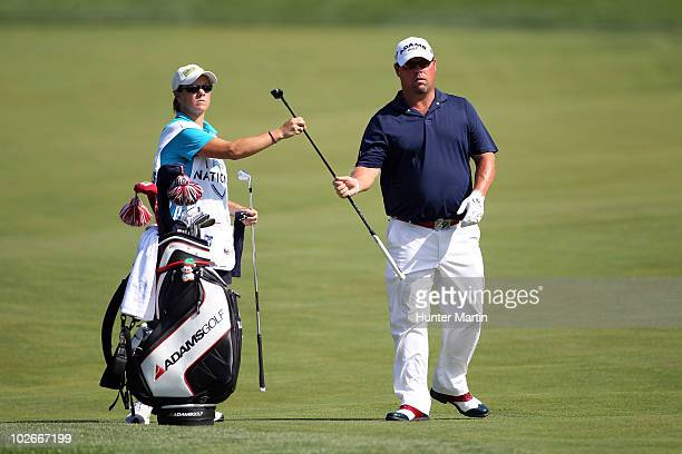 Kris Banks is handed a club by his caddie AJ Eathorne during the final round of the ATT National at Aronimink Golf Club on July 4 2010 in Newtown...