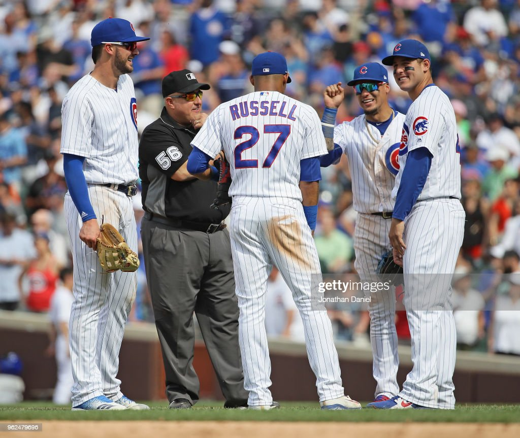 Kris Bryant #17, Addison Russell #27, Javier Baez #9 and Anthony Rizzo #44 of the Chicago Cubs share a laugh with second base umpire Eric Cooper #56 during a pitching change against the San Francisco Giants at Wrigley Field on May 25, 2018 in Chicago, Illinois. The Cubs defeated the Giants 6-2.