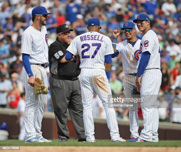 Kris Bryant Addison Russell Javier Baez and Anthony Rizzo of the Chicago Cubs share a laugh with second base umpire Eric Cooper during a pitching...