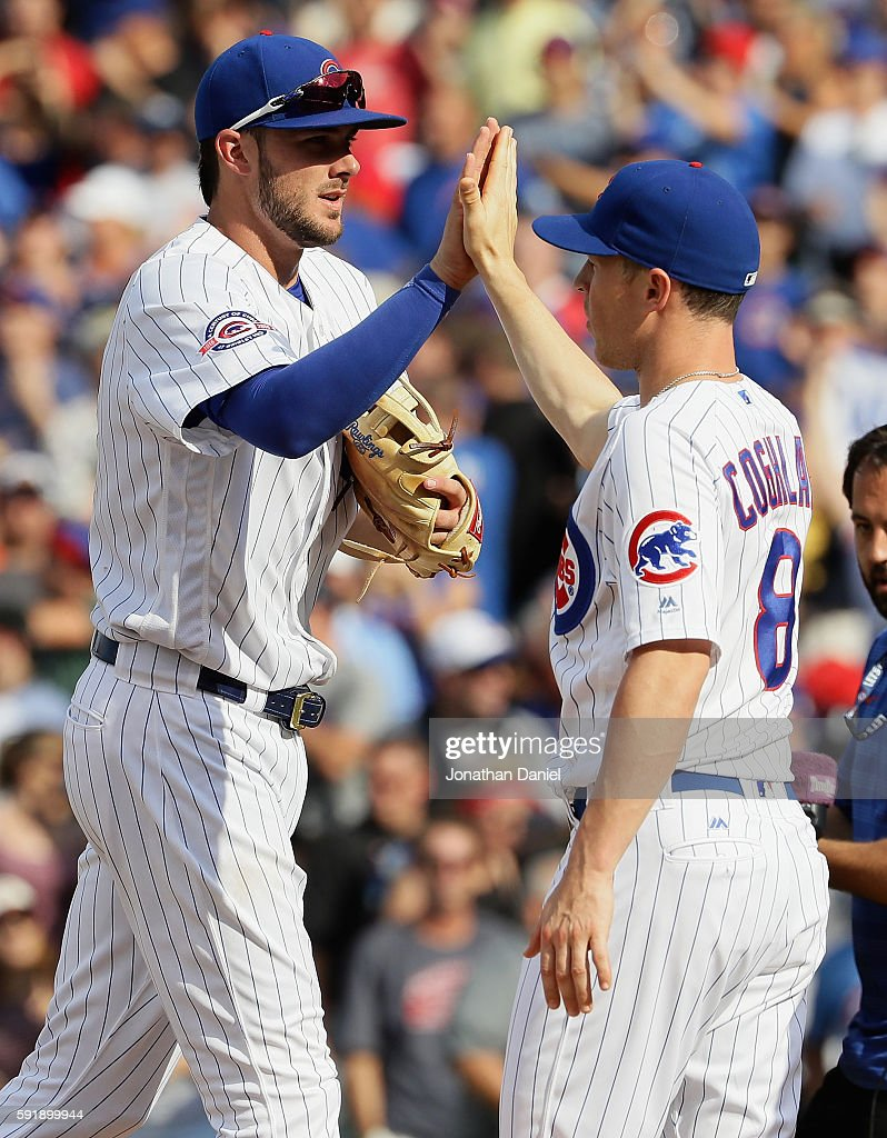 Kris Bryant #17 (L) and Chris Coghlan #8 of the Chicago Cubs celebrate a win over the Milwaukee Brewers at Wrigley Field on August 18, 2016 in Chicago, Illinois. The Cubs defeated the Brewers 9-6.
