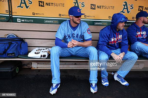 Kris Bryant and Matt Szczur of the Chicago Cubs sit in the dugout before the game against the Oakland Athletics at the Oakland Coliseum on Saturday...
