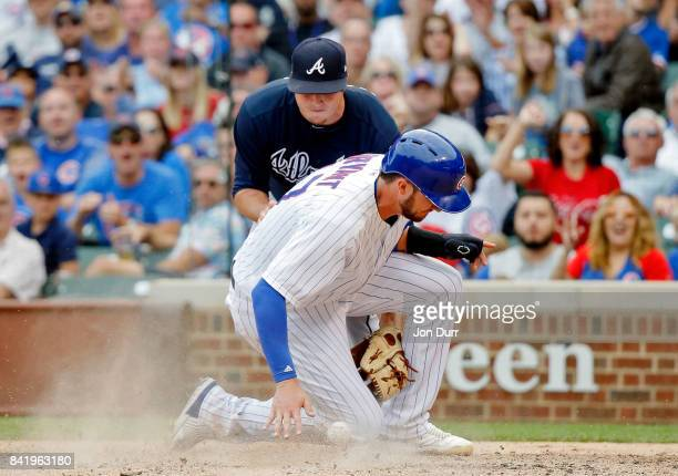Kris Bryant of the Chicago Cubs beats the throw and scores after a wild pitch by Luke Jackson of the Atlanta Braves at Wrigley Field on September 2...