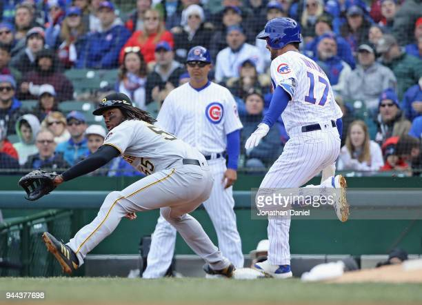 Kris Bryant of the Chicago Cubs beats the throw to Josh Bell of the Pittsburgh Pirates for a hit in the first inning during the Opening Day home game...