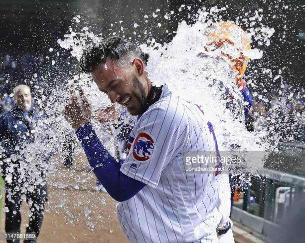 Kris Bryant of the Chicago Cubs gets dunked by Javier Baez after he hit the game-winning three run home run in the bottom of the 9th inning against...