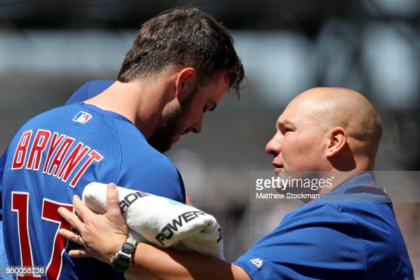 Kris Bryant of the Chicago Cubs is attended to by trainer Matt Johnson after being hit with a pitch in the first inning against the Colorado Rockies...