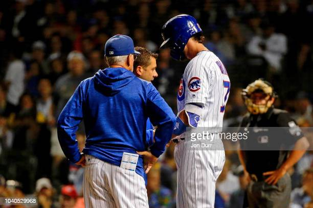 Kris Bryant of the Chicago Cubs is tended to by head athletic trainer PJ Mainville and manager Joe Maddon after being hit by a pitch during the...