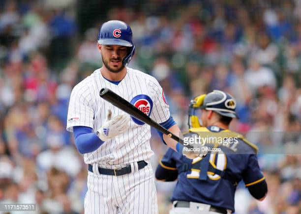Kris Bryant of the Chicago Cubs looks down at his bat after striking out during the first inning of a game against the Milwaukee Brewers at Wrigley...