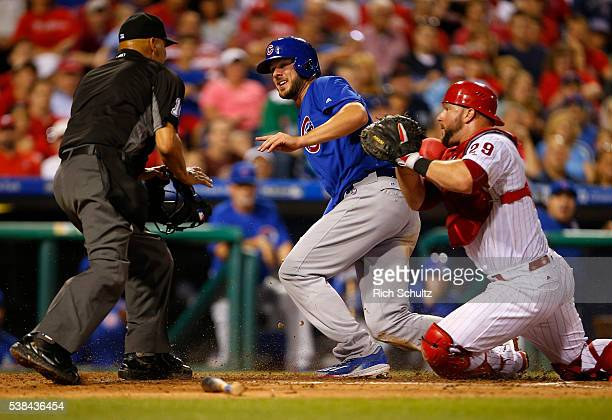 Kris Bryant of the Chicago Cubs looks to home plate umpire Vic Carapazza who rules him safe on a fielder's choice off the bat of Matt Szczur as...