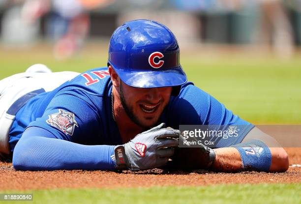 Kris Bryant of the Chicago Cubs reacts as he holds his left hand after being tagged out while trying to steal third base against Johan Camargo of the...