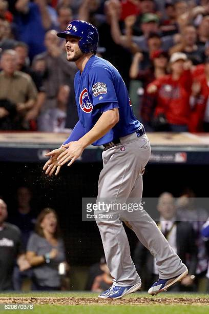 Kris Bryant of the Chicago Cubs reacts as he scores a run on a sacrifice fly ball hit by Addison Russell during the fourth inning against the...