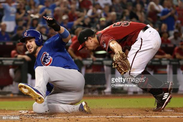 Kris Bryant of the Chicago Cubs safely slides into home plate to score a run past starting pitcher Zack Godley of the Arizona Diamondbacks during the...